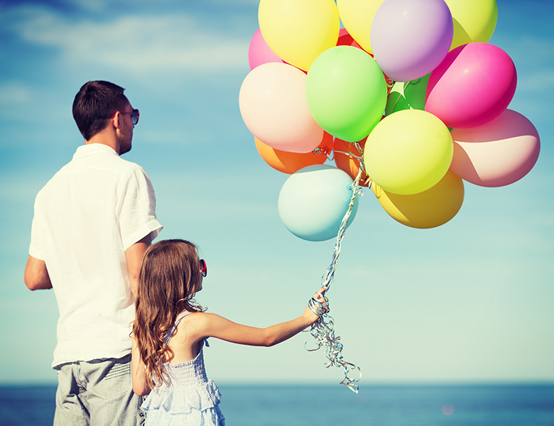 Father and daughter holding balloons. Mindful parenting.