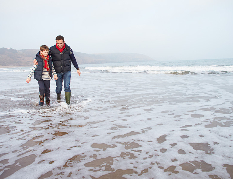 Father and son walking on a beach. Mindful parenting tips for fathers.