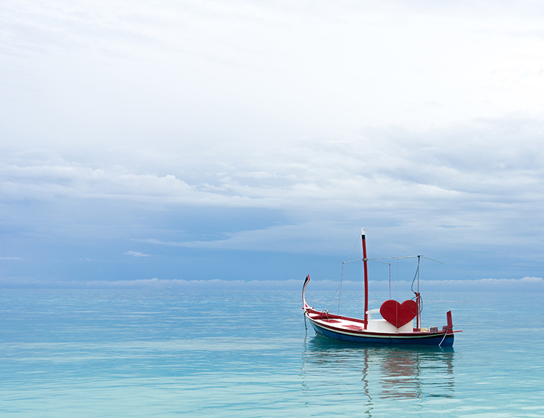 A boat in a large sea of water with a red heart, waiting for a couple to take a romantic ride.